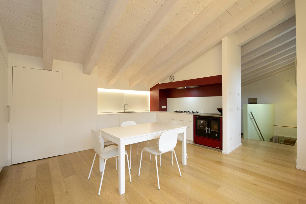 Cucina su misura in mansarda in legno laccato bianco e tavolo da pranzo su misura - Corazzolla