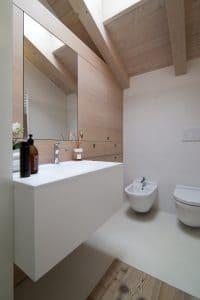 Arredo bagno su misura in legno di larice rigato con lavabo in corian bianco - Corazzolla