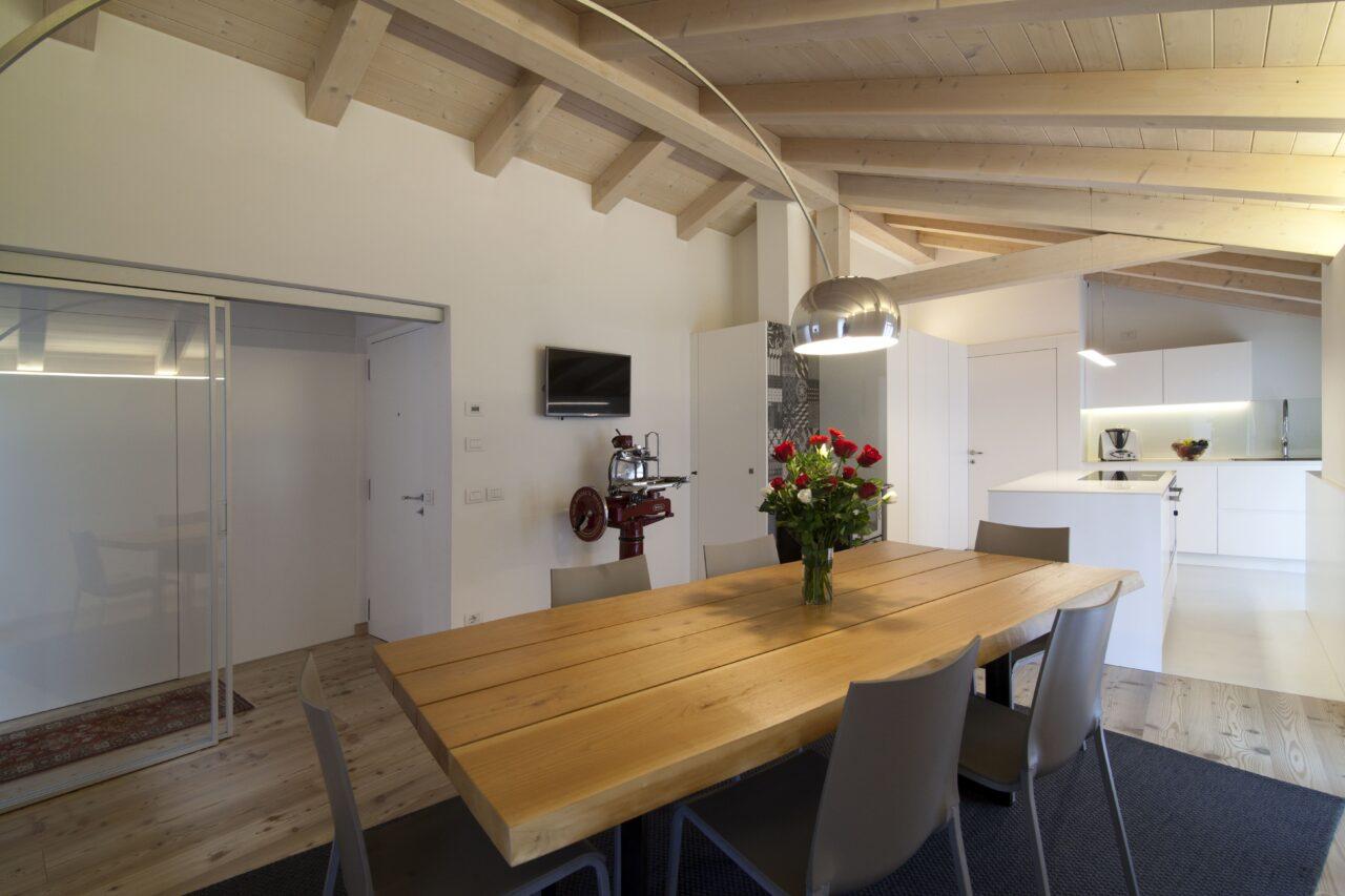 Arredo cucina mansarda su misura in laccato bianco con tavolo in legno di ciliegio - Corazzolla
